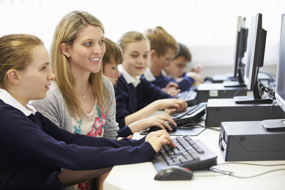 teacher and children in school computer class