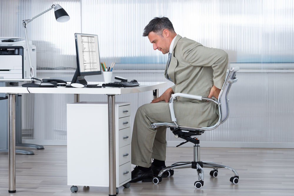 Man Holding Back Sat In Office Chair